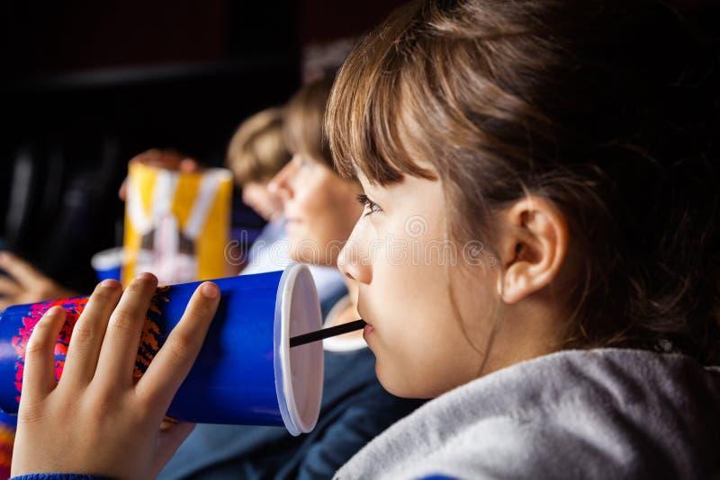 Flicka som dricker Cola, medan hålla ögonen på film i teater arkivbild