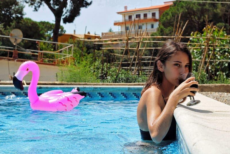 Flicka som dricker en sodavatten i pölen royaltyfri foto