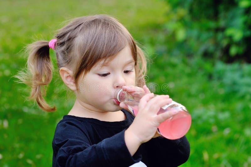 Flicka som dricker från en flaska av lemonad, utomhus arkivbilder