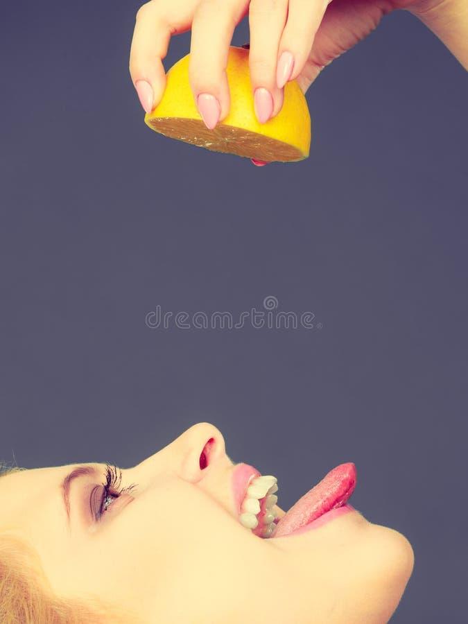 Flicka som dricker fruktsaft från saftig citronfrukt arkivfoto