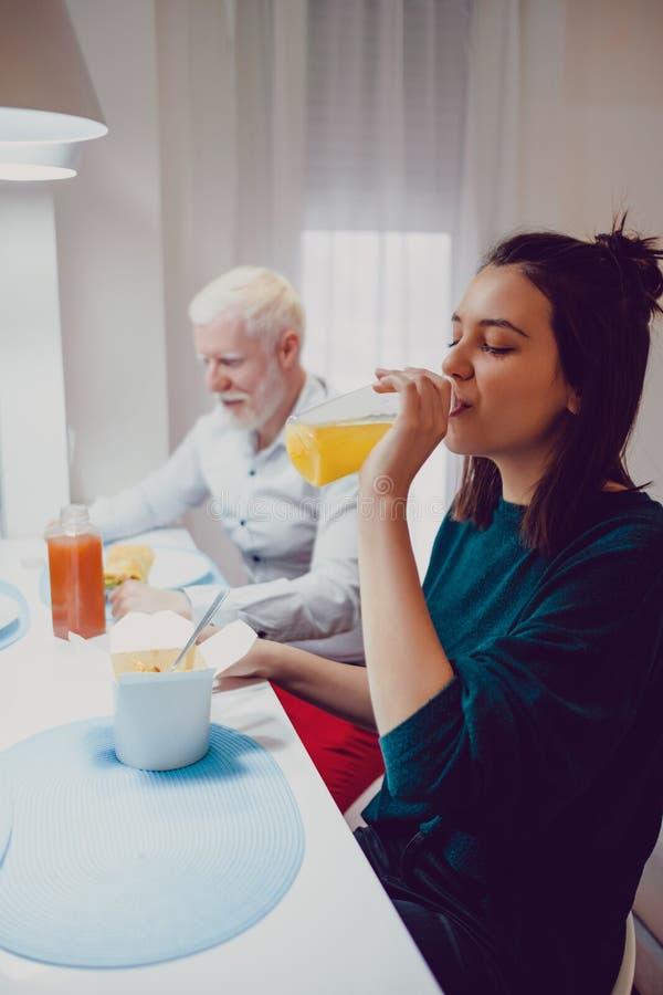 Flicka som dricker fruktsaft på matställen med vännen arkivfoton
