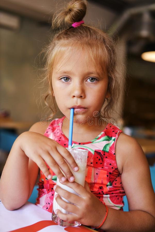 Flicka som dricker milkshake royaltyfria foton