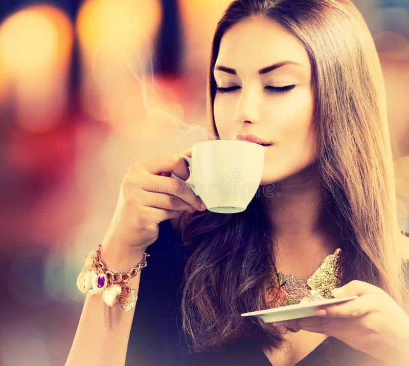 Flicka som dricker te eller kaffe arkivbild