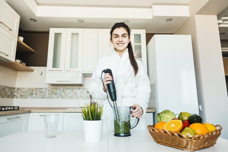 Flicka som förbereder exponeringsglas av Smoozie royaltyfri bild