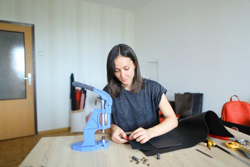 Flicka som förbereder läder för framställning av handväskan royaltyfri fotografi
