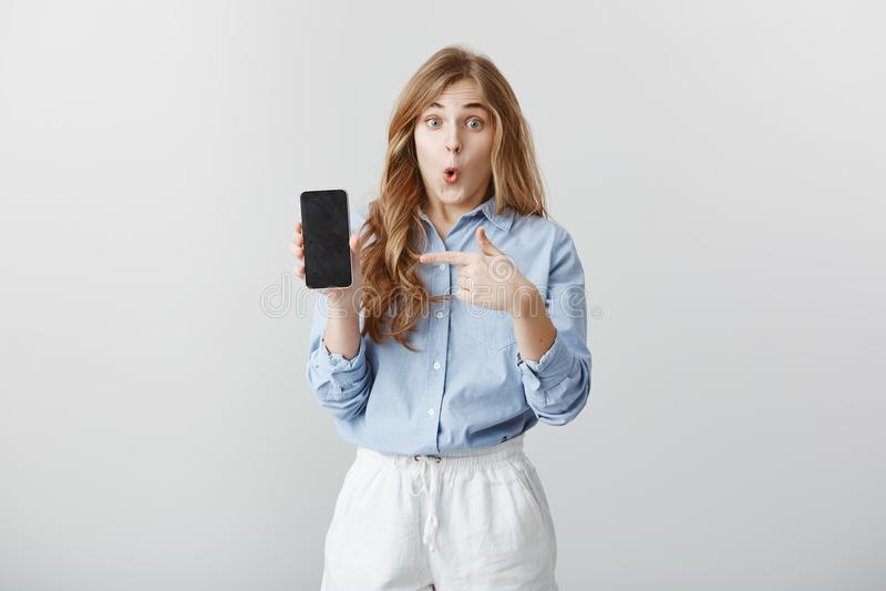 Flicka som förbluffas med den nya telefonen Stående av den fascinerade chockade unga europeiska kvinnan med blont hår i blusvisni arkivbilder