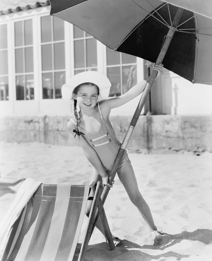 Flicka som förlägger ett stort paraply in i sanden (alla visade personer inte är längre uppehälle, och inget gods finns Leverantö arkivbilder