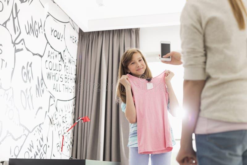 Flicka som försöker på kläder medan syster som fotograferar hennes hemmastatt royaltyfria foton