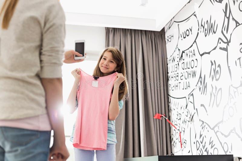 Flicka som försöker på kläder medan syster som fotograferar hennes hemmastatt royaltyfri bild