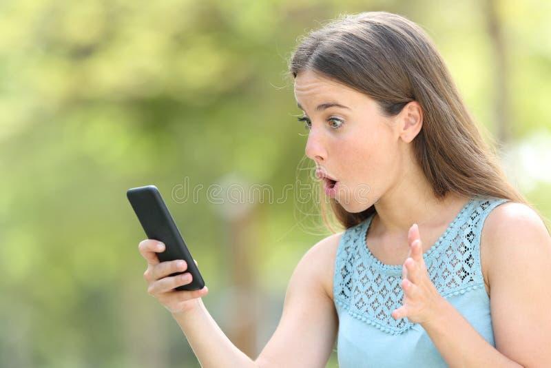 Flicka som finner förvåna online-innehållet på den smarta telefonen arkivfoto