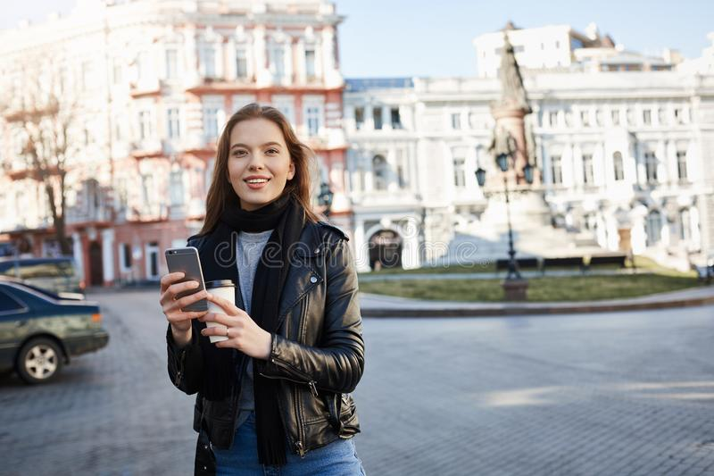 Flicka som finner hennes väg i stad Stående av den charmiga caucasian kvinnlign i moderiktig dräkt som går på gatan som ler på arkivbilder