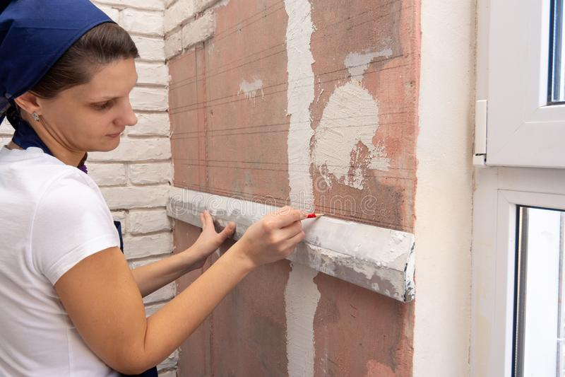 Flicka som fodrar en vägg för att imitera murverk royaltyfri bild