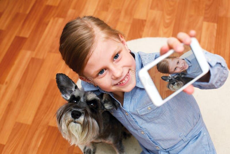 Flicka som fotograferar sig och hennes hund royaltyfria bilder