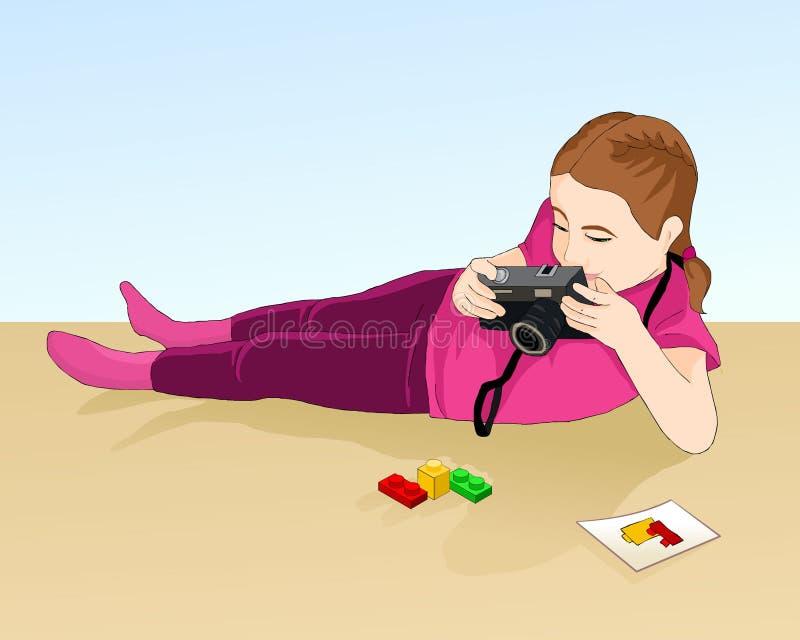 Flicka som fotograferar stycken av Lego Ung fotograf royaltyfria bilder