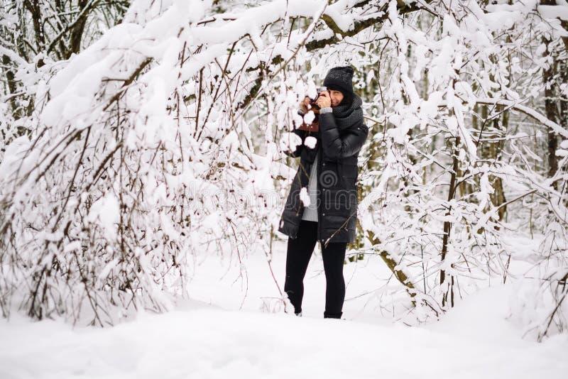 Flicka som fotograferas i snöig skog arkivbild