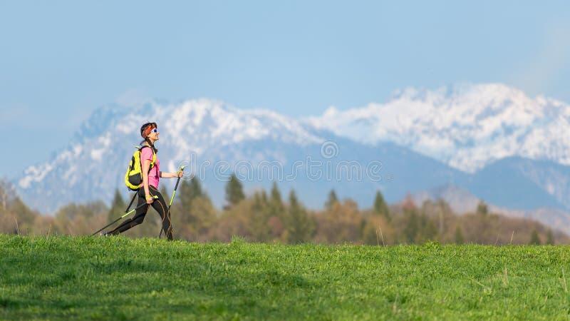 Flicka som fotvandrar i bergen med vårkontraster av gröna ängar och snö på bergen arkivbilder