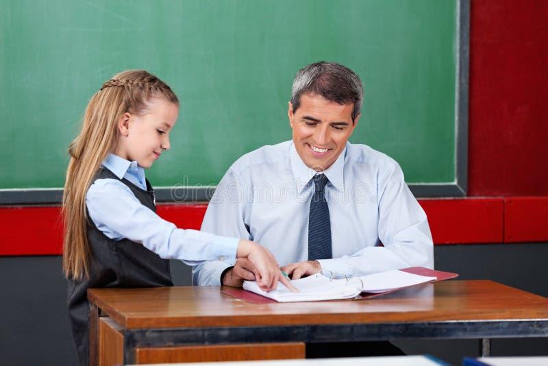 Flicka som frågar fråga till den manliga läraren At Desk royaltyfri fotografi