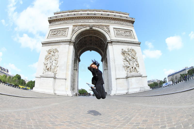 Flicka som framme hoppar av Arc de Triomphe royaltyfri fotografi