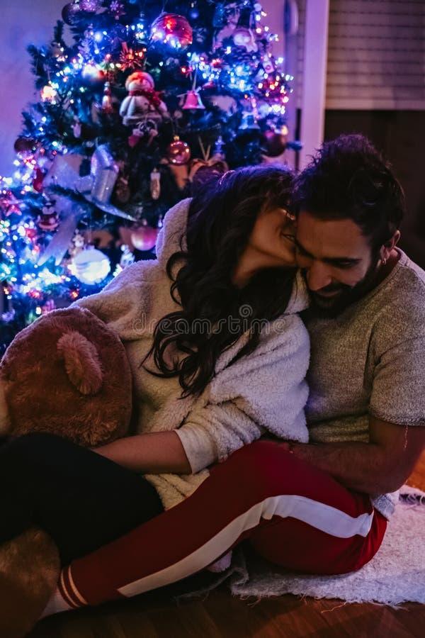 Flicka som framme kysser pojkvännen av julgranen arkivfoto