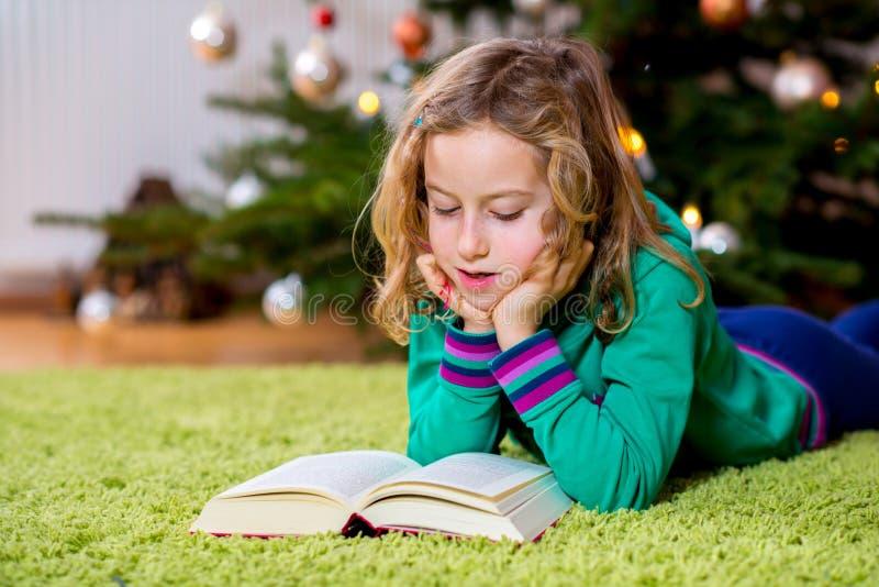 Flicka som framme läser en bok av julträdet arkivbild