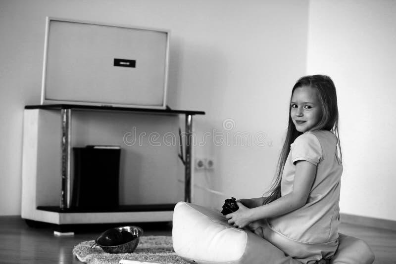 Flicka som framme spelar av TV:N royaltyfri fotografi