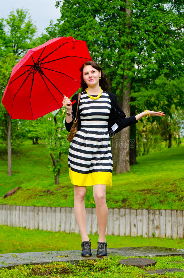 Flicka som går efter regnet arkivbild