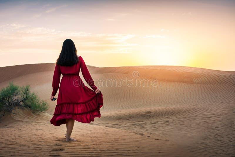 Flicka som går i öknen på solnedgången royaltyfri foto