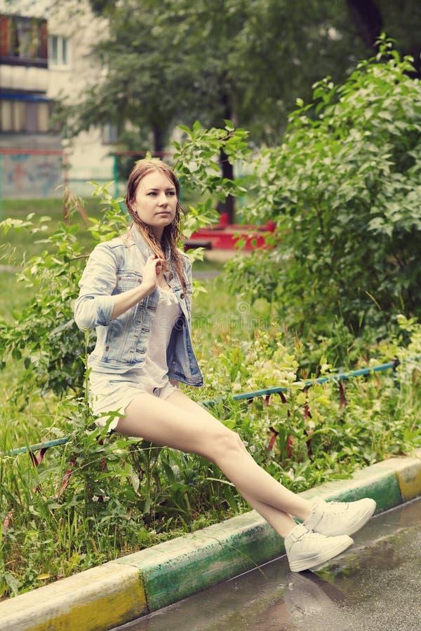Flicka som går i regnet fotografering för bildbyråer