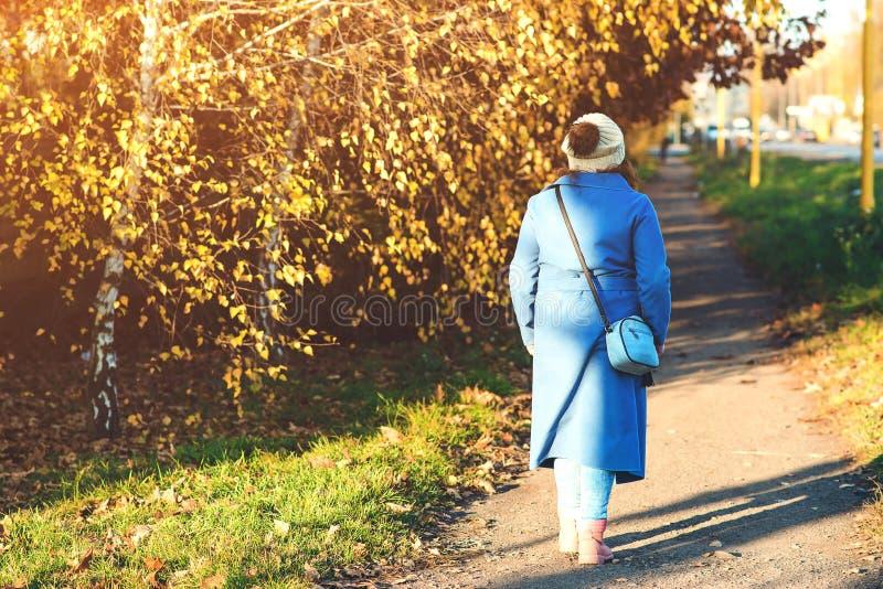 Flicka som går i stadsgata Soligt väder för härlig höst Ung kvinna som tycker om hösten, tillbaka sikt alla några individuella ob royaltyfri bild
