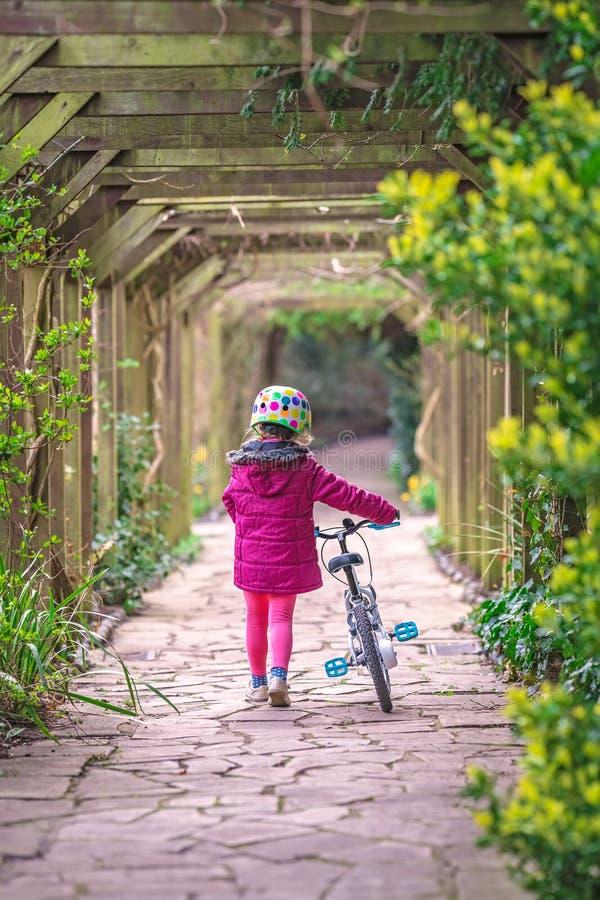 Flicka som går med hennes cykel arkivbilder