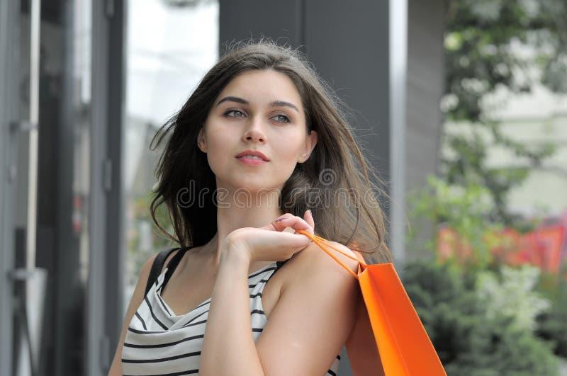 Flicka som går med shoppingpåsar arkivbilder
