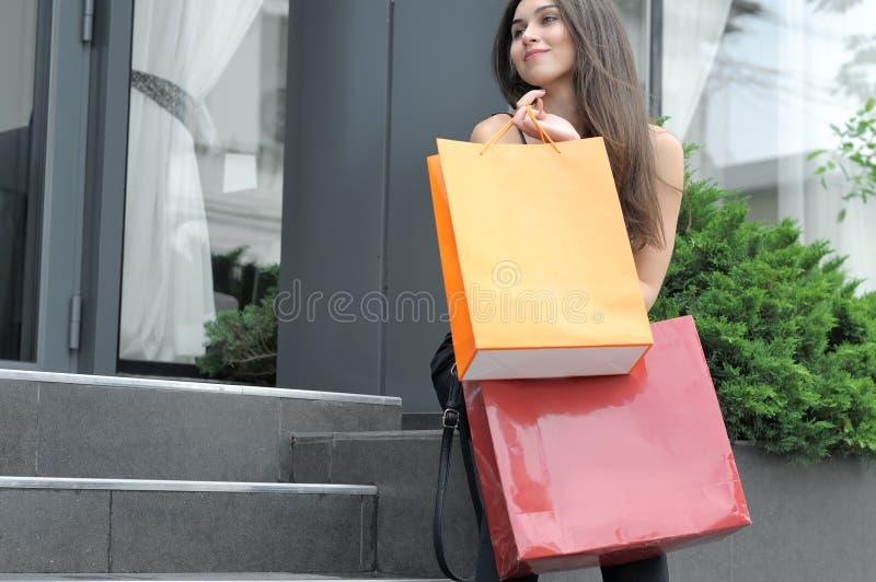 Flicka som går med shoppingpåsar arkivfoto