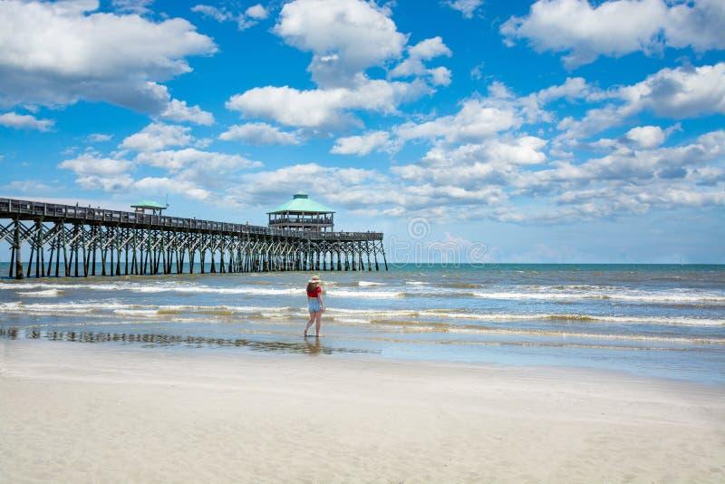 Flicka som går på den härliga stranden på sommarsemester royaltyfria bilder