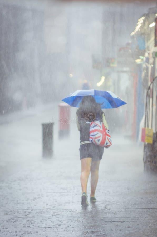Flicka som går på sommarregn i staden arkivfoto