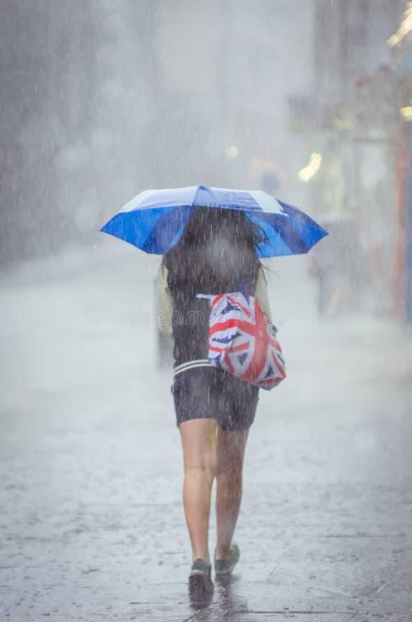 Flicka som går på sommarregn i staden royaltyfri fotografi