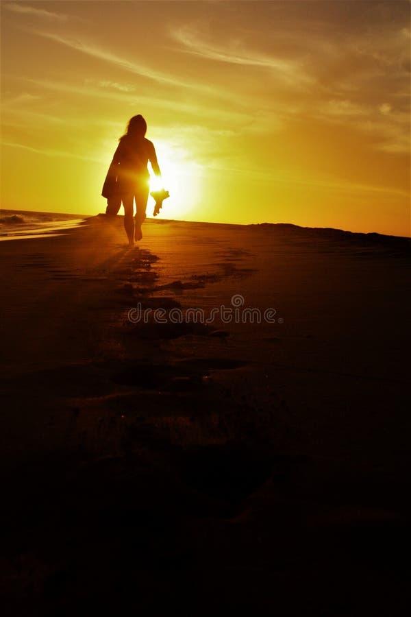 Flicka som går på stranden i solnedgången arkivbild