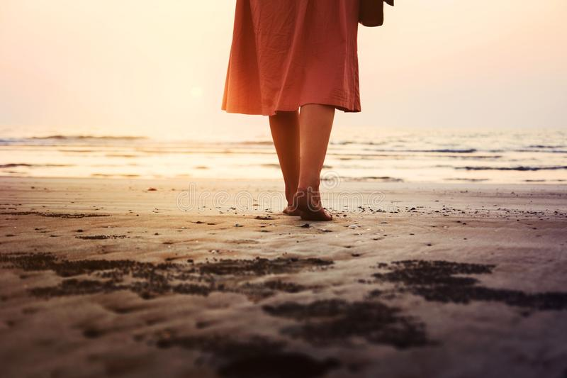 Flicka som går på stranden på solnedgången royaltyfri fotografi