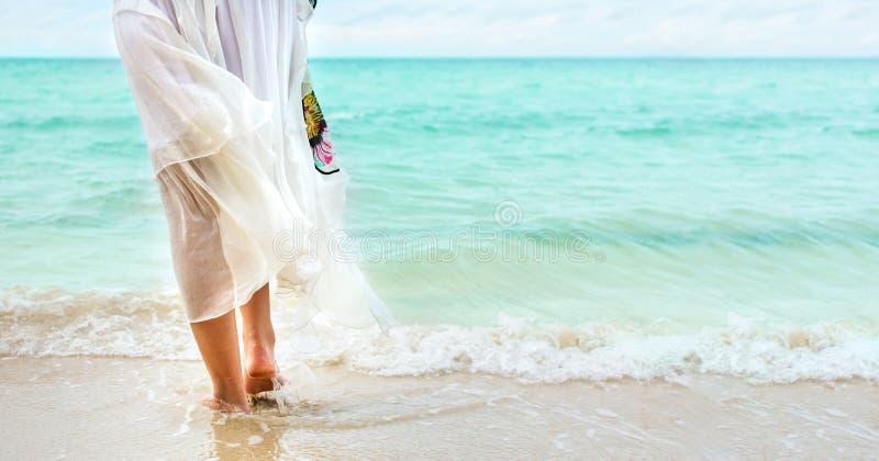 Flicka som går till den bärande vita klänningen för hav arkivfoton