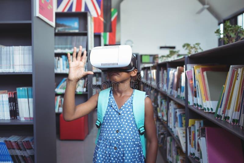 Flicka som gör en gest, medan bära virtuell verklighetsimulatorn arkivfoto