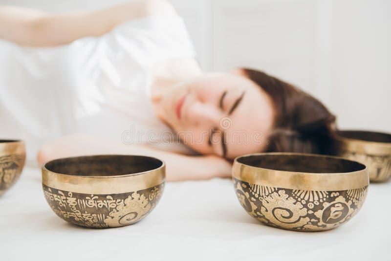 Flicka som gör massageterapi som sjunger bunkar i Spa royaltyfria bilder