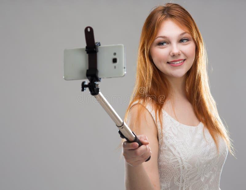 Flicka som gör selfie med din telefon royaltyfria bilder