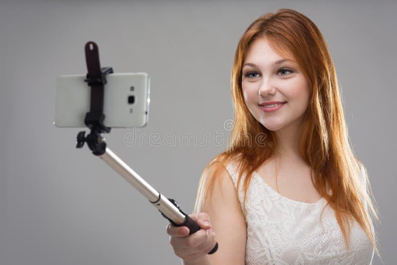 Flicka som gör selfie med din telefon arkivbild