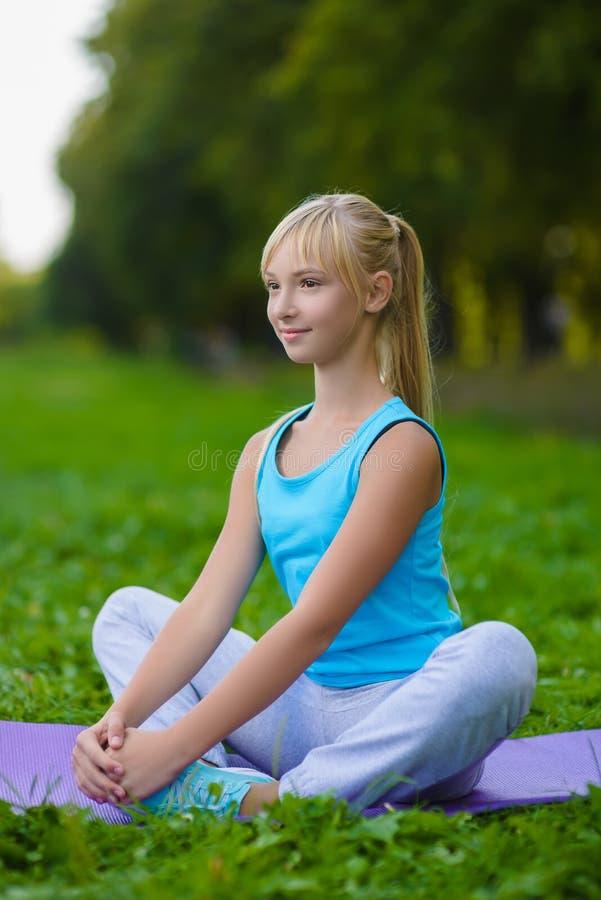 Flicka som gör utomhus- gymnastiska övningar eller att öva arkivbild