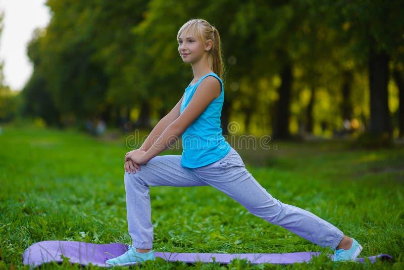 Flicka som gör utomhus- gymnastiska övningar eller att öva royaltyfri fotografi