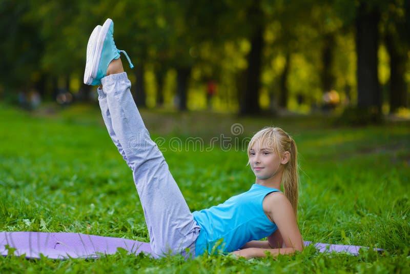 Flicka som gör utomhus- gymnastiska övningar eller att öva royaltyfria foton