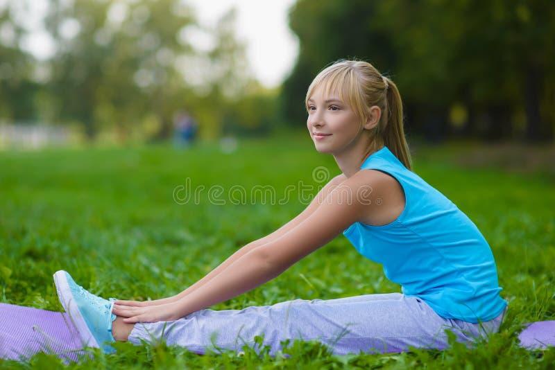 Flicka som gör utomhus- gymnastiska övningar eller att öva fotografering för bildbyråer