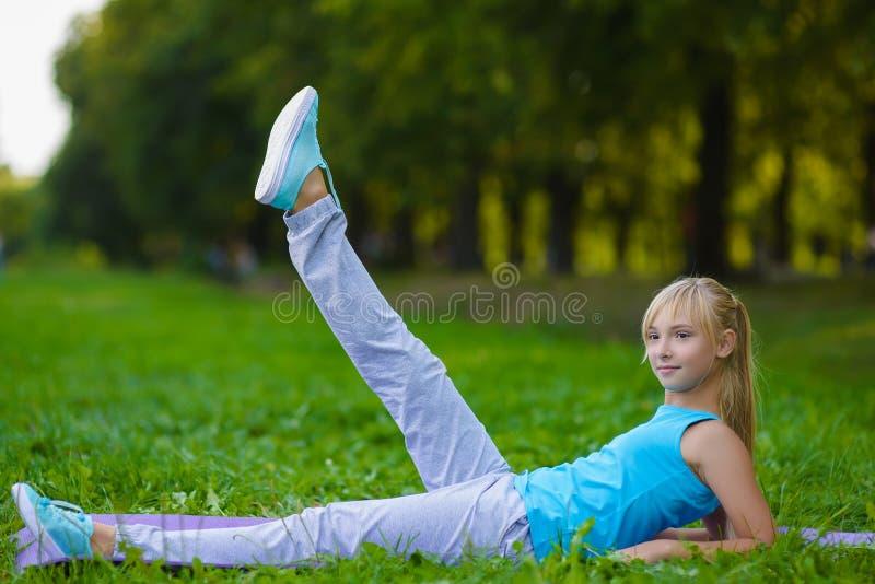 Flicka som gör utomhus- gymnastiska övningar eller att öva royaltyfri bild