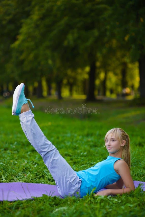Flicka som gör utomhus- gymnastiska övningar eller att öva arkivfoto