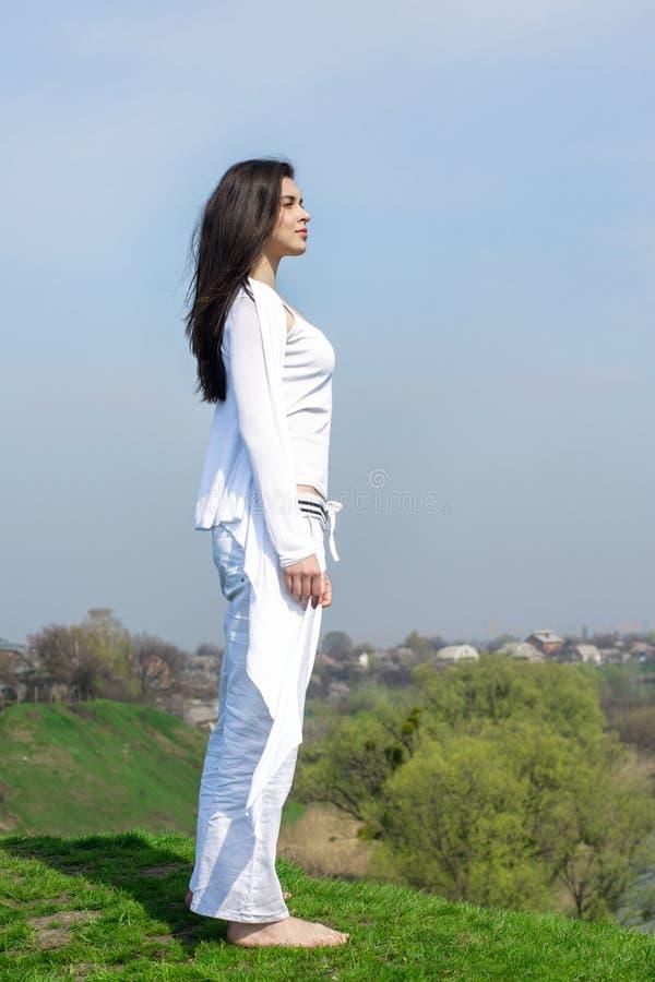 Flicka som gör yogaövningsanseende på en kulle royaltyfri foto