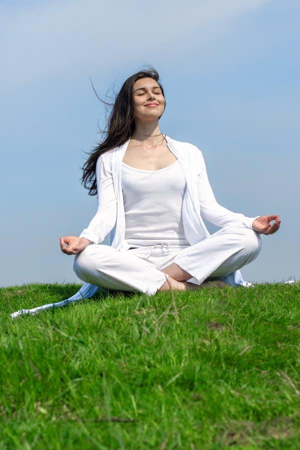 Flicka som gör yogaövningsanseende på en kulle royaltyfria bilder